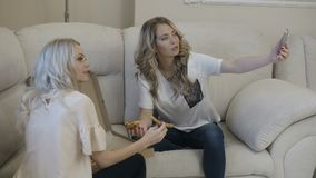 Girls make selfie with pizza. Two blonde girls make selfie with slices of pizza stock video footage