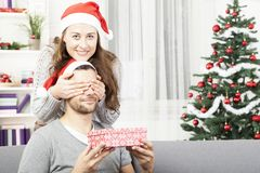 Girls makes her boyfriend a christmas gift Royalty Free Stock Image
