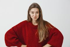 Girls making bet how long they can hold breath. Indoor shot of childish attractive feminine woman in stylish red loose. Sweater, holding hands on hips and Stock Image