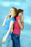 Girls making calls. Two teenage girls back to back making phone calls on cell phones outside against a blue sky Royalty Free Stock Photo