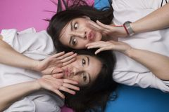 Girls making faces isolated. Beautiful attractive cool girls making faces isolated on pink and blue Royalty Free Stock Photo