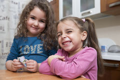 Girls making faces. Two cute kids smiling and making faces at camera in kitchen Stock Image