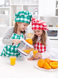 Girls making freshly squezed orange juice Stock Photography