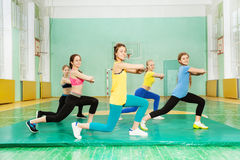 Girls making long step forward in sports hall. Side view picture of smiling teenage girls  exercising in sports hall, making long step forward Royalty Free Stock Photography