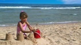 Girls making sandcastles on beach stock video