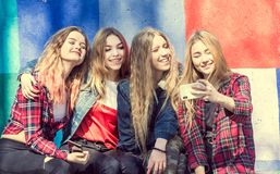 Girls making selfie outdoors while sitting on longboards Royalty Free Stock Images