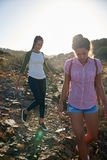 Girls making their way down hillside Stock Image