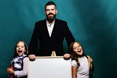 Girls and man with happy faces. Kids wearing schoolbags royalty free stock  photography 873b3b33a