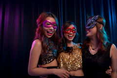 Girls in masquerade masks. Happy excited girls wearing masquerade ball masks royalty free stock photography