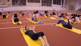 Girls on the mats at the gym doing exercise Stock Images