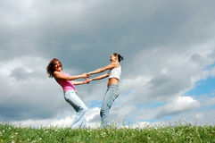 Girls on the meadow. Girls hold each other for the hands and rotate Royalty Free Stock Photos