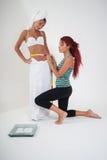 Girls measuring the waistline Royalty Free Stock Photography