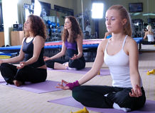Girls meditating in fitness club Royalty Free Stock Photos