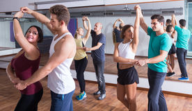 Girls and men learning salsa. Young sporty girls and men learning latino steps Stock Photography
