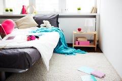 Girls messy bedroom. Modern messy bedroom of teenage girl: comfortable bed with laptop, headphones, blanket hanging down and school books lying on floor stock photos