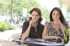 Girls met at lunch. Two girls sitting in a cafe and discuss the passers and drinking wine Royalty Free Stock Photos