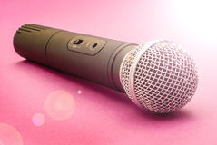 Microphone. Hand help microphone for singing on brint pink background with shiny light Royalty Free Stock Photo