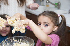 Girls mixing dough with hands Royalty Free Stock Photography