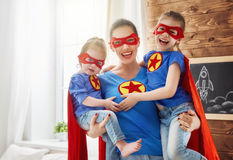 Girls and mom in Superhero costumes royalty free stock photography