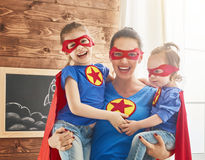 Girls and mom in Superhero costumes. Mother and her children playing together. Girls and mom in Superhero costumes. Mum and kids having fun, smiling and hugging Royalty Free Stock Photo