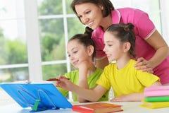 Girls and mother  doing homework. Cute  tweenie girls and mother   doing homework at home Royalty Free Stock Photography