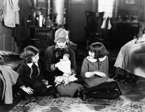Girls and mother on floor with doll Stock Photo