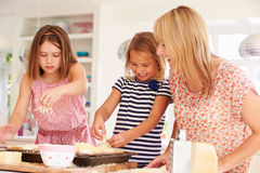 Girls With Mother Making Cheese On Toast Royalty Free Stock Images