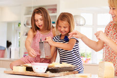 Girls With Mother Making Cheese On Toast Stock Image