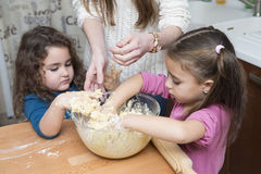 Girls and mother mixing dough with hands Royalty Free Stock Photography