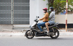 Girls on Motorbike. Always in helmets and masks. Vung Tau, Vietnam Royalty Free Stock Photo