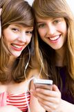 Girls with mp3 player. Two teenage girls listening to MP3 player, sharing headphones, smiling Royalty Free Stock Photos