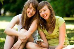 Girls with mp3 player. Two teenage girls listening to MP3 player, sharing headphones, smiling Stock Photo