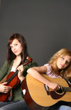 Girls with Musical Instruments. Two teenage sisters with violin and guitar against dark background Stock Image