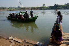 Girls in Myanmar meet boat with tourists on the shore Stock Photo