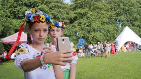 Girls in national costumes with wreaths shooting video on mobile phone, children in embroidery make selfie photo on stock footage