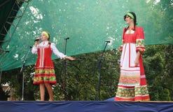 Girls in national suit emerge on scene. Girls in red national suit sing on scene at day of the city Mstyora Stock Image