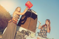 Girls near a car with no fuel. Stock Image