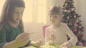 Girls near christmas tree painting ceramic toys. Two girls near a Christmas tree painting ceramic toys stock video