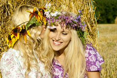 Girls near haystacks with wreaths on their heads Stock Photo