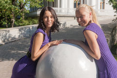 Girls near the stone sphere Stock Image