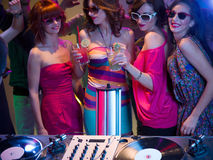 Girls nght out in a nightclub. Close-up of young attractive caucasian girls dancing and having fun at a party with sunglasses and cocktails in their hands, in Royalty Free Stock Photos