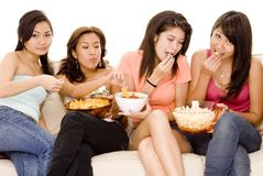 Girls Night In #1. Four pretty young asian women sitting on a sofa with popcorn and nachos Stock Photos