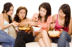 Girls Night In #2. Four pretty young women sit on a sofa with snacks Stock Images