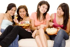 Girls Night In #3. Four attractive young women sitting on a sofa with popcorn and corn chips Royalty Free Stock Photo