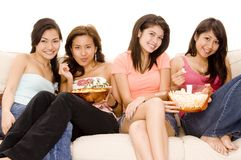 Girls Night In #4. Four cute young women sitting on a sofa with snacks Royalty Free Stock Image