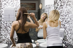 Girls night out. Girls applying makeup in the bathroom of a club Royalty Free Stock Photos