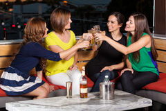 Girls night out. Cute female friends having fun and drinks at a restaurant at night Stock Image
