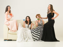 Girls night out. Group of beautiful women sitting together on sofa celebrating with drinks Royalty Free Stock Image