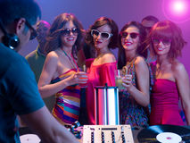 Girls night out at a party. Young attractive caucasian girls dancing and having fun at a party with sunglasses and cocktails in their hands in front of a dj Stock Images