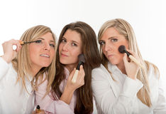 Girls night out. Three young women applying make-up, getting ready to go out Royalty Free Stock Images